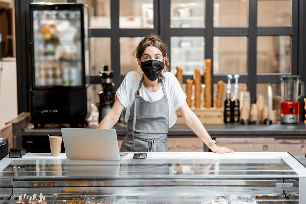 Woman employee at ice cream counter wearing face mask