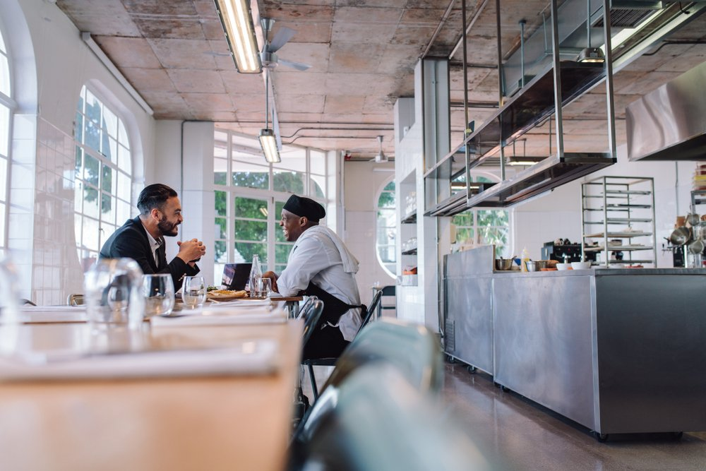 Franchise business consultant talking to a cook in a restaurant kitchen
